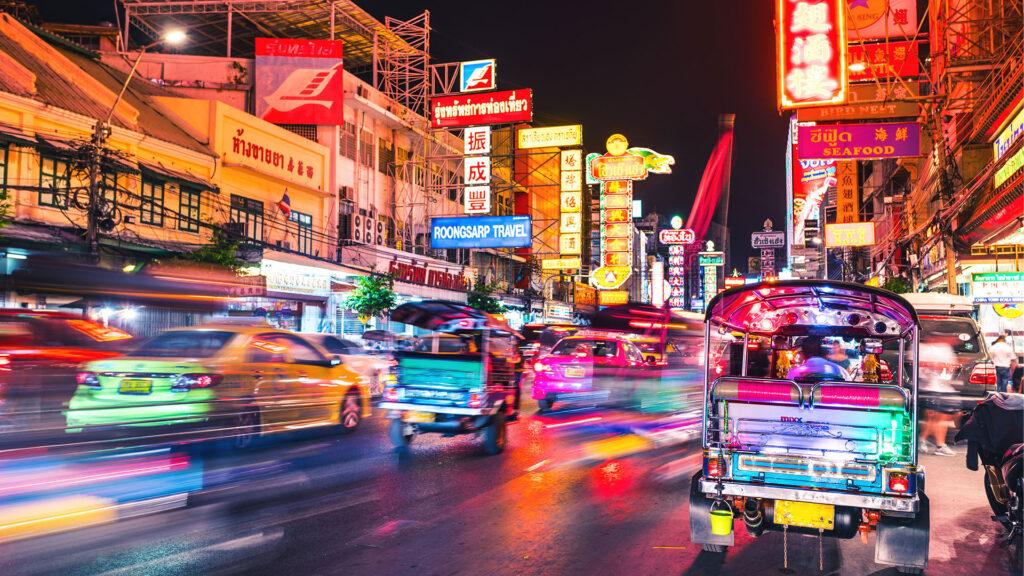 Farbige und hektische strasse in Bangkok mit TukTuks und vielen leuchtenden Werbeplakaten